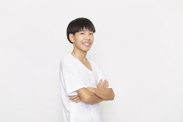 Портрет молодого азиатского подростка студента мужчины в белой рубашке со сложенными руками на белом фоне