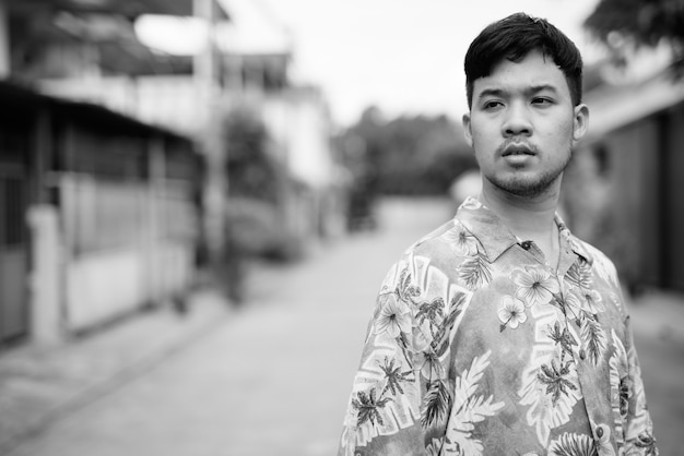 Portrait of young asian tourist man wearing hawaiian shirt in the streets outdoors