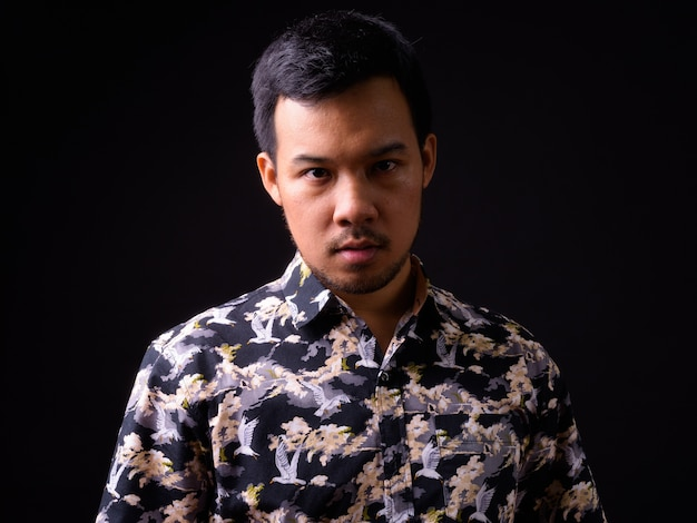 Portrait of young asian tourist man with bohemian shirt on black