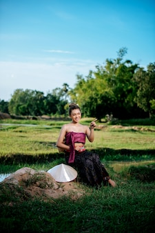 Portrait young asian woman in beautiful thai traditional clothes at rice field