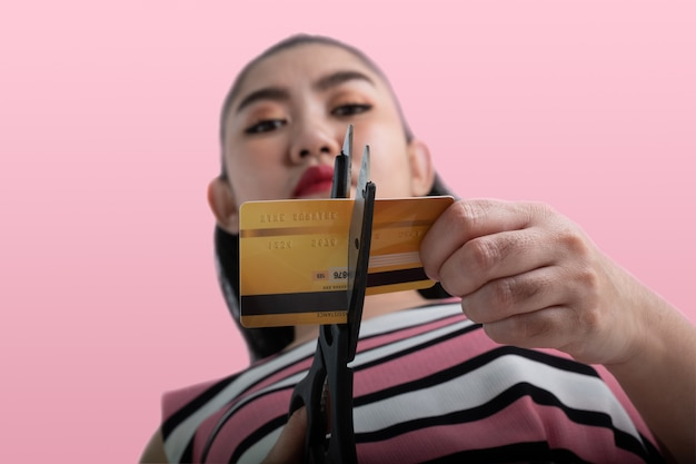Portrait of young asian woman cutting up a credit card with scissors to stop spending on shopping at the pink