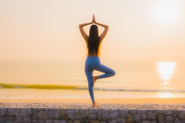 Женщина портрета молодая азиатская делает раздумье вокруг океана пляжа моря на восходе солнца