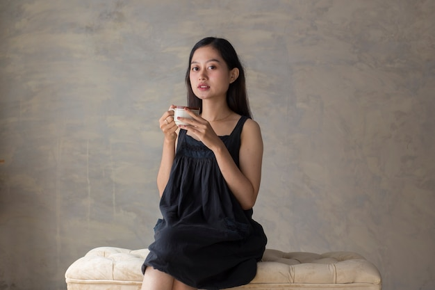 Portrait of young asian woman drinking coffee and relaxing on couch
