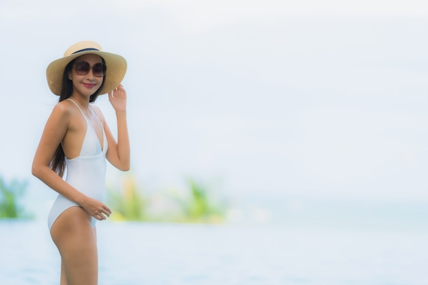 Portrait young asian woman happy smile relax around swimming pool in hotel resort