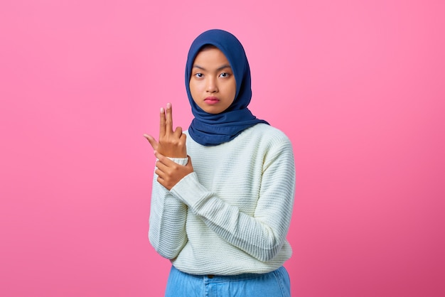 Portrait of young asian woman holding symbolic gun with hand gesture