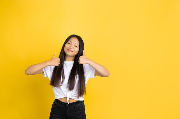 Portrait of young asian woman isolated on yellow studio wall
