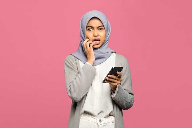 Portrait of young asian woman looking scared and holding mobile phone