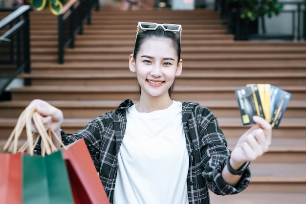 Portrait of young asian woman place eyeglasses on head standing on stairs with multi-colors shopping paper bag