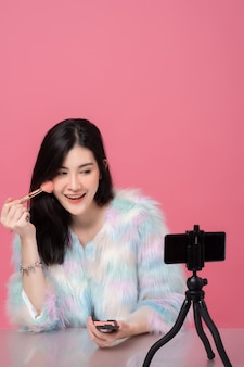 Portrait of young asian woman professional beauty vlogger or blogger recording to share on social media by smartphone on tripod.