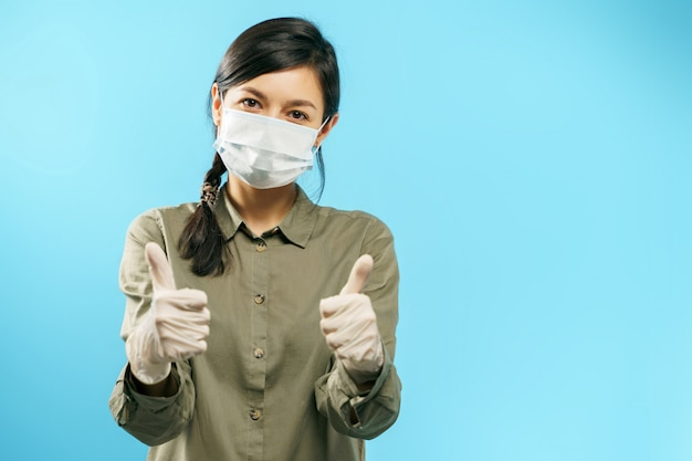 Portrait of a young asian woman in protective medical mask and gloves showing thumb up on blue