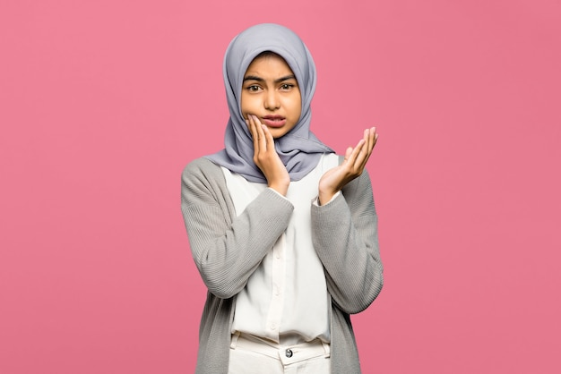 Portrait of young asian woman raising confusedly palm
