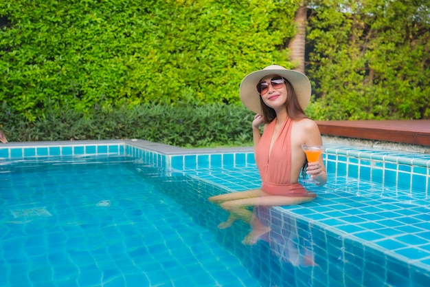 Portrait young asian woman relax happy smile around swimming pool in hotel
