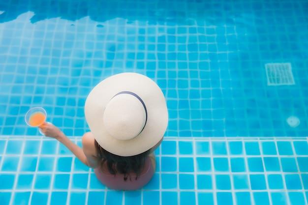 세로 젊은 아시아 여자 호텔 수영장 주위에 행복한 미소를 휴식