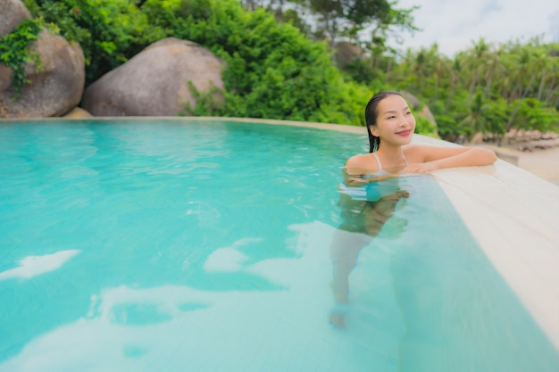 Portrait young asian woman relax smile happy around outdoor swimming pool in hotel resort with sea ocean view