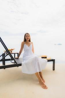 세로 젊은 아시아 여자는 호텔과 리조트 수영장 주위에 미소 행복 휴식