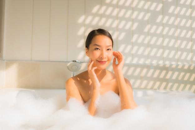 若いアジアの女性の肖像画はリラックスしてバスタブでお風呂