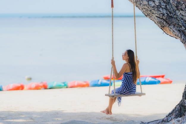 Portrait young asian woman sitting on swing rope and sea around beach sea ocean coconut palm tree