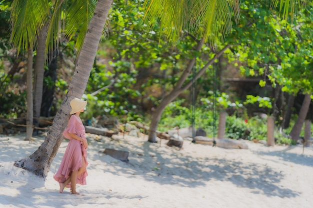 Улыбка женщины портрета молодая азиатская счастливая вокруг океана моря пляжа с пальмой кокоса на каникулы праздника