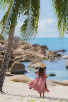 Portrait young asian woman smile happy around beach sea ocean with coconut palm tree for holiday vacation
