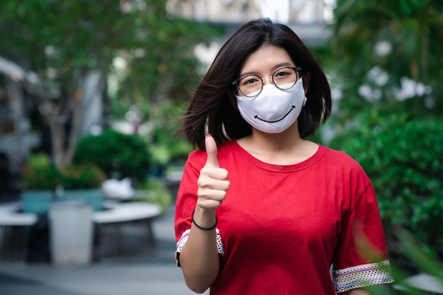 Portrait of young asian woman smiling wear eyeglasses and face mask while walking outdoor with thumb up gesture, healthcare