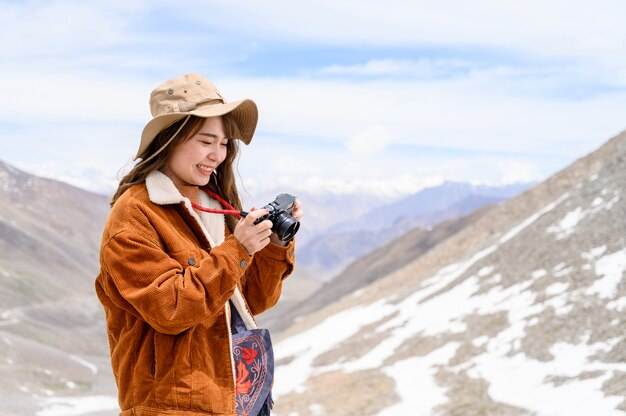 Portrait of young asian woman taking photos on snow mountain