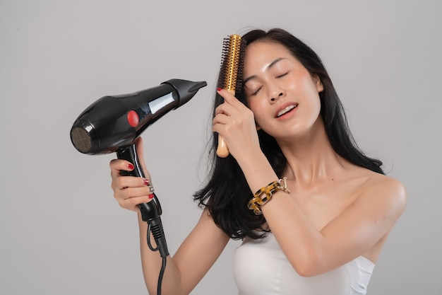 Portrait of young asian woman uses hair dryer on grey