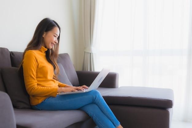 Giovane donna asiatica del ritratto che per mezzo del taccuino del computer portatile sul sofà