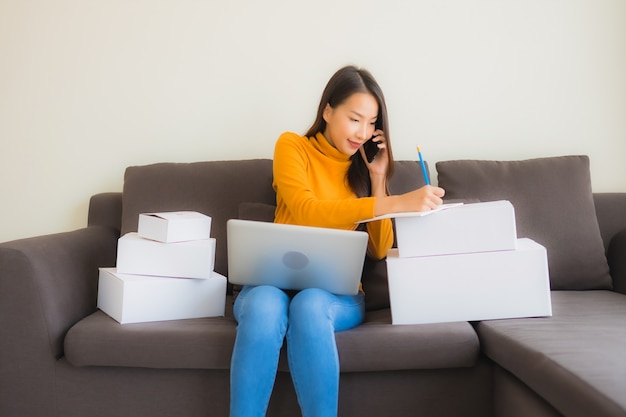 Giovane donna asiatica del ritratto che per mezzo del computer portatile per lavoro con il contenitore di pacchi