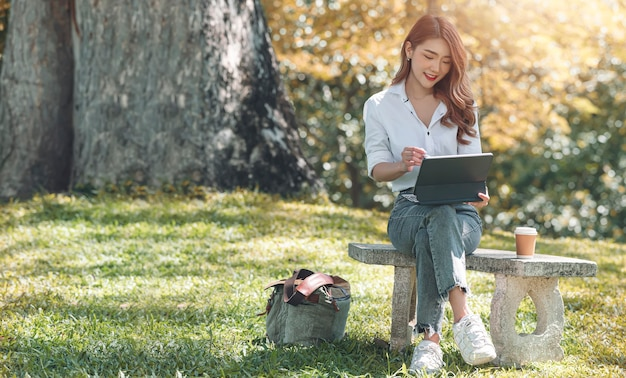 Portrait of young asian woman using tablet computer while sitting at stone bench at park, outdoors activity.
