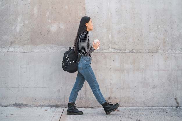 Portrait of young asian woman walking and holding a cup of coffee against grey wall.