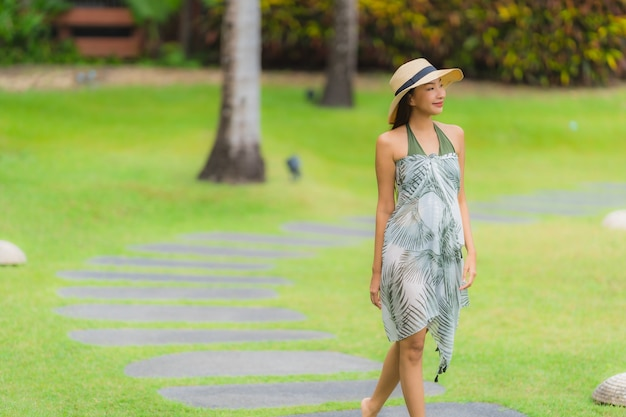 Portrait young asian woman walking on path way in the garden
