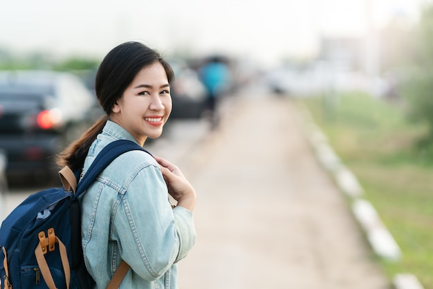 Portrait of young asian woman wearing blue denim jacket and backpack smiling looking back