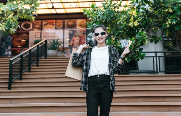 Portrait of young asian woman wearing eyeglasses going down stairs with shopping paper bag
