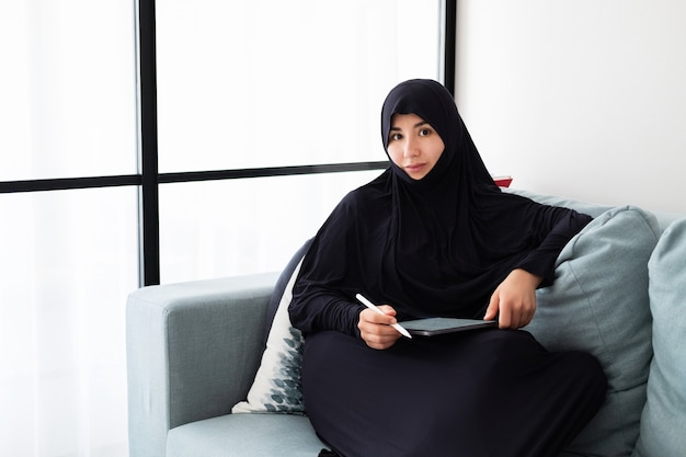 Portrait of young asian woman wearing hijab, working at home with tablet