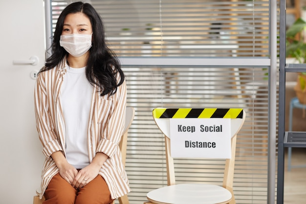 Portrait of young asian woman wearing mask and looking at camera while waiting in line in office with keep social distance sign, copy space