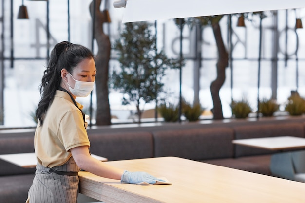 Portrait of young asian woman wearing mask while cleaning tables in modern restaurant interior, covid safety concept, copy space