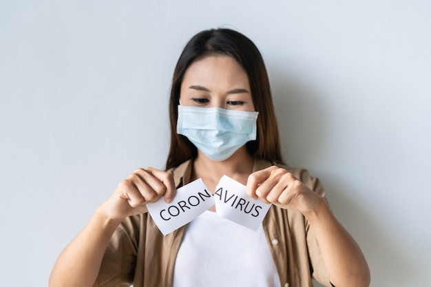 Portrait of young asian woman wearing medical mask tears the paper with the word coronavirus