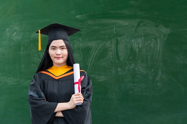 Portrait of young asian woman with graduation diploma next to blackboard