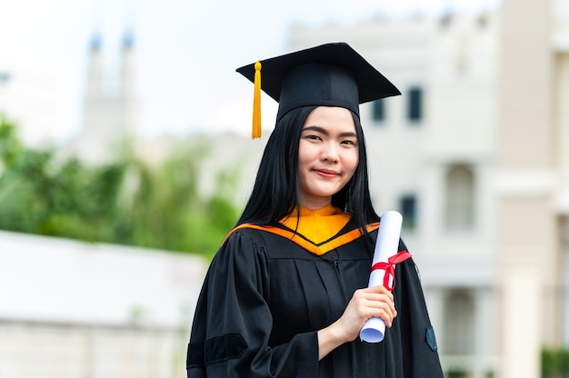 Portrait of young asian woman with graduation diploma outdoors