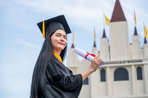 Portrait of young asian woman with graduation diploma outdoors Premium Photo