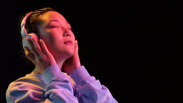 ヘッドフォンで肖像画の若いアジアの女性