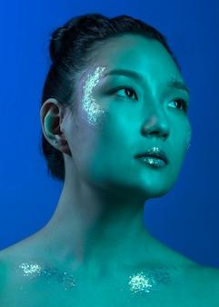 La giovane donna asiatica del ritratto con il professionista compone