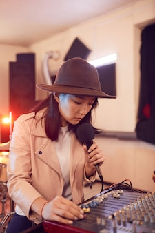 Portrait of young asian woman writing music in recording studio and singing to microphone