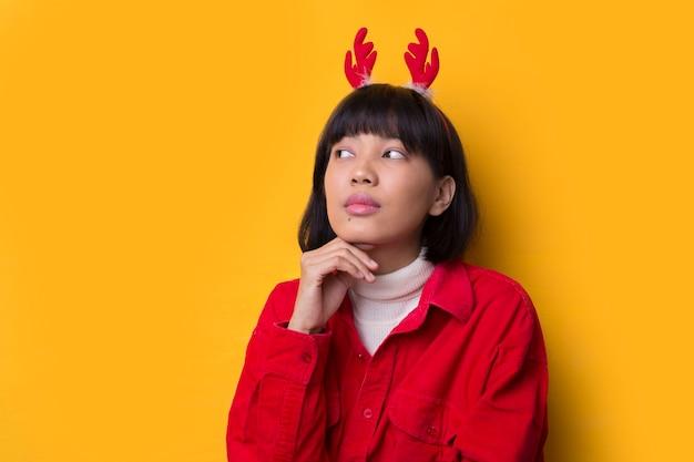 肖像画の若いアジアの女性はサンタのクリスマス帽子をかぶる
