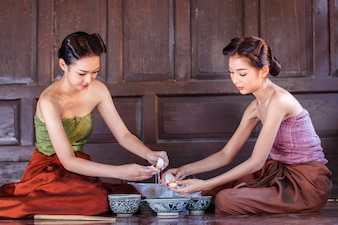 Portrait young asians women dressed in ancient Thailand are helping to make the dessert