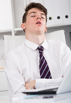 Portrait of young assistant sleeping in the office
