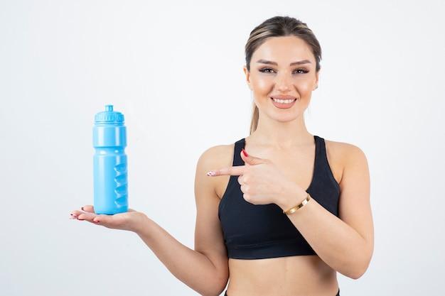 Ritratto di giovane donna atletica che tiene la bottiglia di acqua blu.