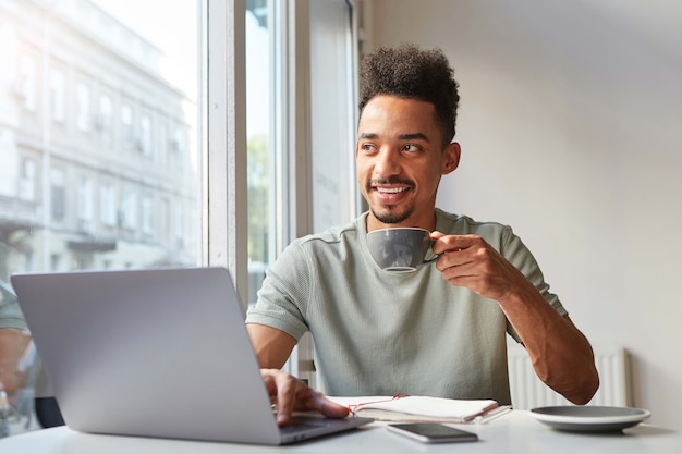 Portrait of young attractive african american smiling boy, sits at a table in a cafe, works at a laptop and drinks aromatic coffee and looks at the window.
