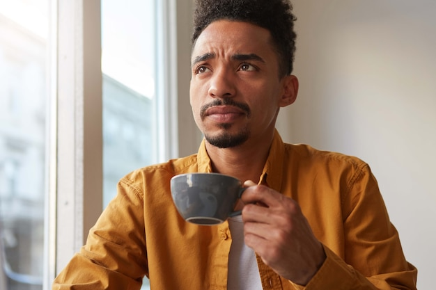 Portrait of young attractive african american thinking boy, drinks aromatic coffee from a gray cup , trying to remember something and thoughtfully looks up.