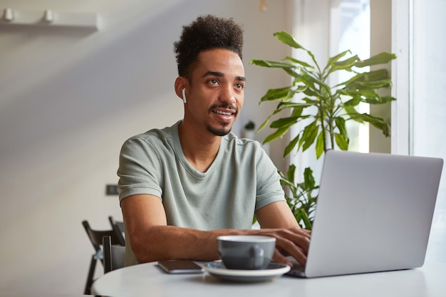 Portrait of young attractive african american thinking boy, sits at a table in a cafe, works at a laptop